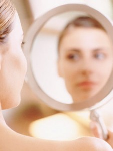 a woman who is looking at her self image-in-mirror